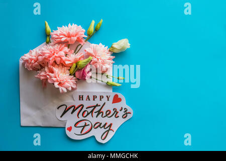 Festive composition with text HAPPY MOTHER'S DAY on candy blue background.Flowers in envelope.Greeting Card with Spring Bouquet. - Stock Photo