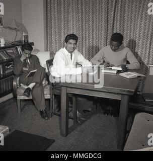 1950s, historical picture shows three male overseas students from the Commonwealth countries at their British lodgings studying, London, England, UK. Post-war Britain saw a big rise in the number of people from overseas coming to work, study and live in the country. - Stock Photo