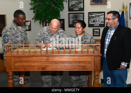 """Col. Roman Hund, installation commander, signs a National American Indian Heritage Month proclamation in Building 1305 at Hanscom Air Force Base, Mass., Oct. 27, as Chief Master Sgt. Henry Hayes, Jr., Hanscom command chief, Senior Airman Charmaine Good Buffalo and Richard Ruggiero, members of the committee, look on. November is National American Indian Heritage Month, a time to recognize the contributions made by American Indian and Alaska Native people. The theme for this year's monthlong observance is """"Standing Together."""" (U.S. Air Force photo by Mark Herlihy) - Stock Photo"""