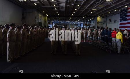 170915-N-AC117-386 YOKOSUKA, Japan (Sept. 15, 2017) The newest Chief Petty Officers march in review at the end of a Chief Petty Officer pinning ceremony on board the Navy's forward-deployed aircraft carrier, USS Ronald Reagan (CVN 76). Ronald Reagan provides a combat-ready force that protects and defends the collective maritime interests of the U.S. and its allies and partners in the Indo-Asia-Pacific region. (U.S. Navy photo by Mass Communication Specialist 3rd Class Macadam Kane Weissman/Released) - Stock Photo