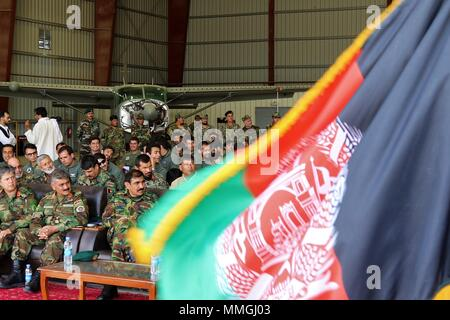 KANDAHAR AIRFIELD, Afghanistan (May 7, 2018) -- As the flag of Afghanistan blows in the breeze, Afghan Airmen watch a graduation ceremony for their fellow airmen with the Kandahar Air Wing on Kandahar Airfield, Afghanistan, May 7, 2018.  The graduation recognized the completion of mission qualification training for 15 UH-60 Pilots and 16 Special Mission Operators.  (U.S. Army photo by Maj. Richard Barker, Train, Advise, and Assist Command-South Public Affairs.) - Stock Photo