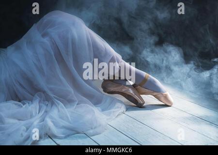The feet of ballerina in the smoke. Beautiful classic dance background. - Stock Photo