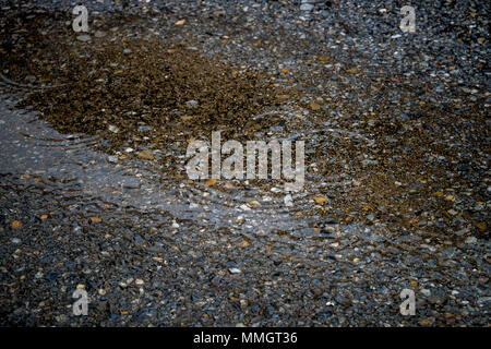 abstract texture background rain drops rippling in a puddle with blue sky reflection - Stock Photo