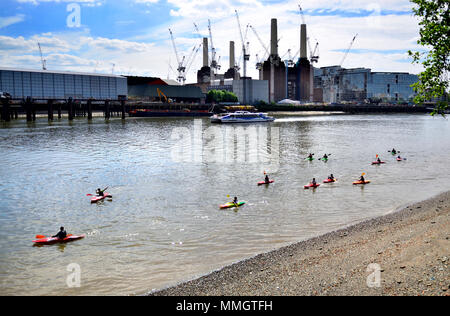 London,England, UK. Batersea Power Station and construction cranes seen from the North bank of the River Thames. Group of children in canoes - Stock Photo