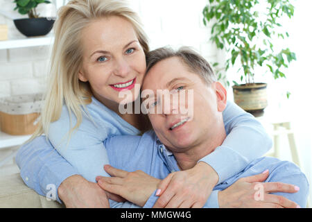 Close up photo of cheerful excited happy happily happy with toothy shining smile blond attractive woman and man, she is hugging him from the back and kisses - Stock Photo