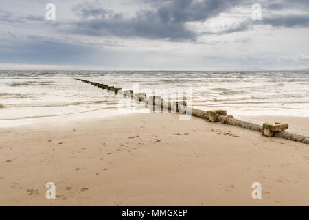 Sewage or waste water discharge pipe leading out to sea on Harlech beach North Wales - Stock Photo
