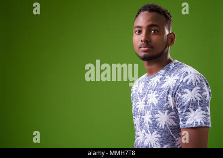 Young handsome African man against green background - Stock Photo