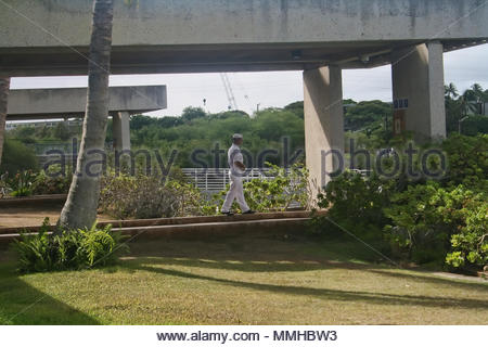 A sailor walks along the grounds of the visitor center at Pearl Harbor in Hawaii. - Stock Photo