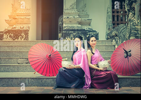 Portrait of beautiful Thai women in Thai national dress sitting on the naga ladder in front of the temple and hold white flowers. They smiles and look - Stock Photo