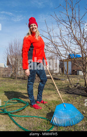 Young charming female gardener stands in her garden on blue sky background, closeup garden tools, vertical picture - Stock Photo