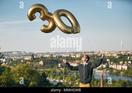 Man celebrates thirty years birthday. Person holding helium balloons in shape of number 30 against city. - Stock Photo