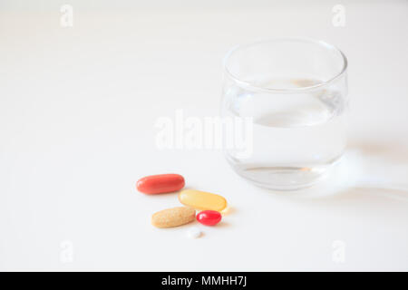 selective focus on a glass of water and medicine pills on white table background - Stock Photo