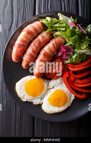 Breakfast Pigs in blankets fried sausages wrapped in bacon, eggs, sauce and fresh salad close-up on a plate. Vertical top view from above - Stock Photo