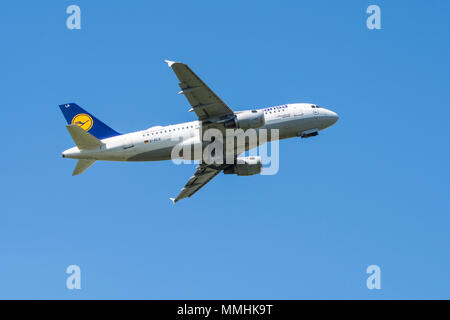 Airbus A319-100, narrow-body, commercial passenger twin-engine jet airliner from Lufthansa German Airlines in flight against blue sky - Stock Photo