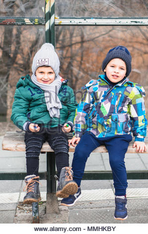 Two young boys sitting and waiting on a wooden bench of a bus stop in Poznan, Poland - Stock Photo