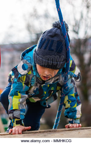Young boy with warm hat and jacket climbing on a equipment with rope at a playground in Poznan, Poland - Stock Photo