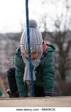 Young boy with warm hat climbing on a equipment at a playground in Poznan, Poland - Stock Photo