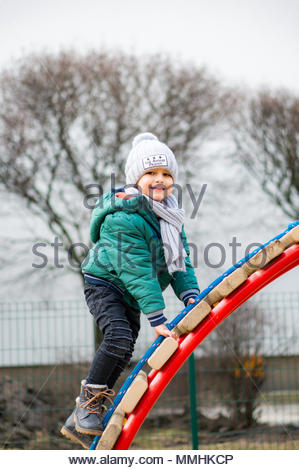 Smiling boy with hat and scarf on a equipment at a playground in Poznan, Poland - Stock Photo