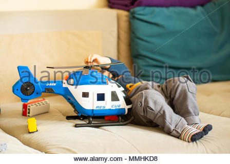 Toy plastic rescue helicopter next to a baby boy on a couch - Stock Photo