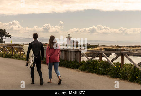 Surfer and friend walking towards the Santa Cruz Surfing Museum and Lighthouse in springtime. West Cliff Drive, Santa Cruz, Northern California, USA. - Stock Photo
