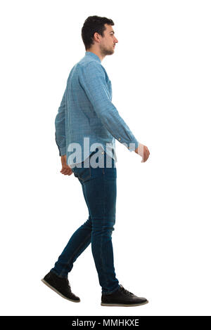 Full length profile shot of a young confident man walking isolated on white background - Stock Photo