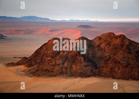 Mountains and red sand dunes of the Namib Desert at dawn, Namib-Naukluft National Park, Sossusvlei area, Sesriem, Namibia - Stock Photo