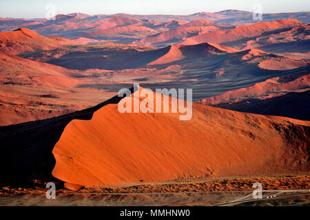Orange and red sand dunes of the Namib Desert at dawn, Namib-Naukluft National Park, Sossusvlei area, Sesriem, Namibia - Stock Photo