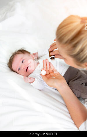 beautiful young mother is giving her cute baby daughter homeopathic globules - Stock Photo