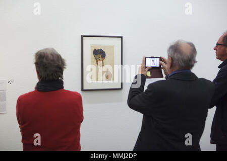 Visitors in front of the drawing 'Self-Portrait with Stripped Shirt' (1910) by Austrian expressionist painter Egon Schiele displayed at his retrospective exhibition in the Leopold Museum in Vienna, Austria. The exhibition marking the centenary of the death of Egon Schiele runs till 4 November 2018. - Stock Photo