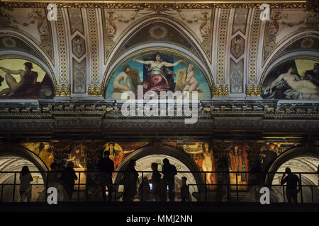 Visitors observe mural paintings by Austrian painter Gustav Klimt from the Klimt Bridge (Klimtbrücke) temporary installed on the main staircase of the Kunsthistorisches Museum (Museum of Art History) in Vienna, Austria. The museum invites visitors to take a closer look at mural paintings from 1890 displayed twelve metres above ground to mark the centenary of the death of Gustav Klimt in 2018. Lunettes by Austrian painter Hans Makart are seen above. - Stock Photo