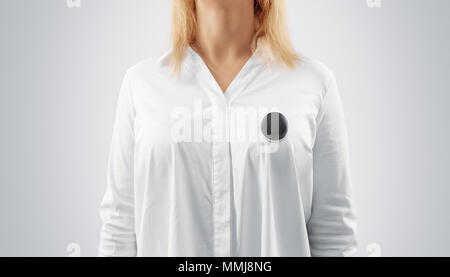 Blank black button badge mockup pinned on the womans chest, close up view. Girl wear white shirt and grey campaign pin mock up. Volunteer round emblem design element. Person with voting symbol - Stock Photo