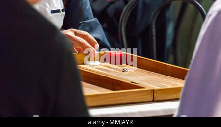 Greek senior men playing backgammon sitting outdoors of an old cafe in Larissa City. - Stock Photo