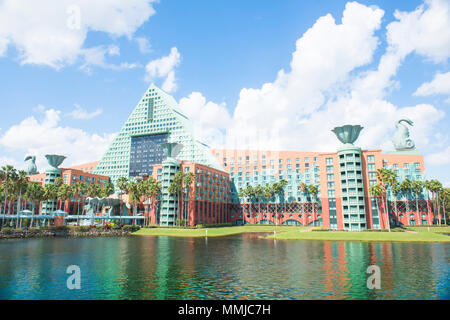 View of the Deluxe Dolphin Hotel, seen from the Epcot-to-Dolphin-Hotel Boardwalk. Sunny blue-sky day. Fluffy white clouds. Colorful water reflection. - Stock Photo