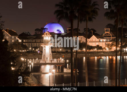 Night view of blue-lit Spaceship Earth and Epcot Boardwalk seen from a room balcony at the Dolphin Hotel. Lighthouse & colorful water reflections. - Stock Photo