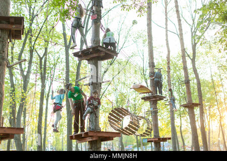 adventure climbing high wire park - people on course in mountain helmet and safety equipment In The Gorky Park Kharkov Ukraine May 2018 - Stock Photo