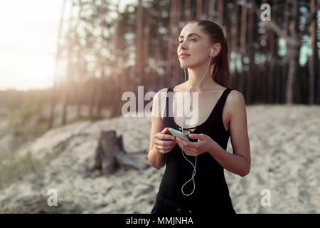 Pretty young girl smiling with pleasure as she listens to music with her eyes almost closed in bliss enjoying the summer sunshine Hipster woman on the - Stock Photo