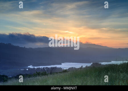 Foggy Cloudy Sunset over Crystal Springs Reservoir as seen from a vista point off Highway 280 in Springtime. - Stock Photo