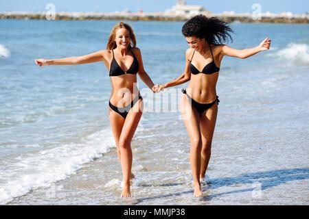 Two young women with beautiful bodies in swimwear on a tropical beach. Funny caucasian and arabic females wearing black bikini walking along the shore - Stock Photo