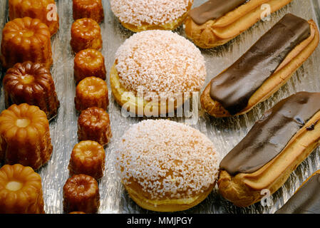 Display of Canelés, Tropezienne Cream Cakes & Chocolate Eclairs Cakes and Pastries in a French Patisserie France - Stock Photo
