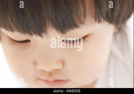Close-up photo of pensive child on a white background - Stock Photo