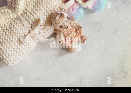 Cute baby clothes for girl. Wowen wrap, booties, teddy bear toy on white background top view copy space - Stock Photo