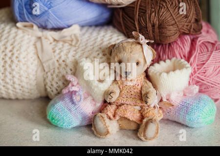 Cute handmade baby clothes for girl's birth. Wowen wrap, booties, teddy bear toy on white background - Stock Photo