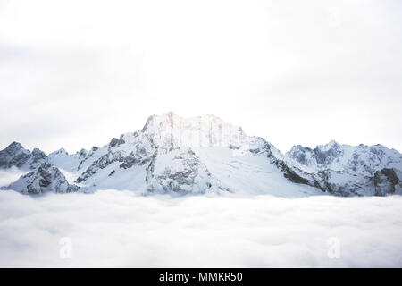Snowy mountains above the clouds. Great winter massif of rocks - Stock Photo