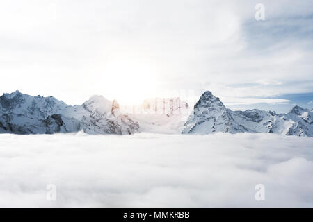 Amazing view of great snow covered winter mountains above the clouds - Stock Photo