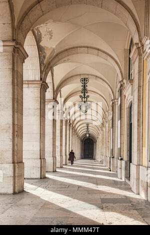 7 March 2018: Lisbon, Portugal - Colonnade in Praca de Comercio, Lisbon, Portugal, one person walking. - Stock Photo