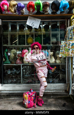 Lady dressed in pink wearing a pink wig poses in front of a wig shop in Brixton Village London SW2 - Stock Photo