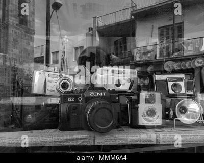 Nicosia, Cyprus - April 26, 2018: An assortment of classic vintage film cameras and flash units displayed in an antique shop window - Stock Photo