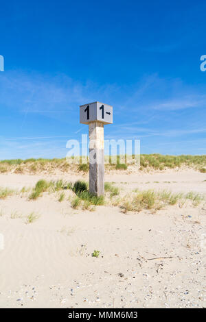 Marked beach pole with number 1 in sand on dune with marram grass on Kennemerstrand beach in IJmuiden, Noord-Holland, Netherlands - Stock Photo