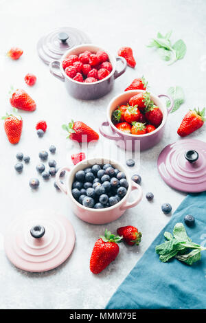 Summer fruit background, top view of berries , smoothie ingredient, inside ceramic colored cocotte, blueberries, strawberries, raspberries, flat lay - Stock Photo