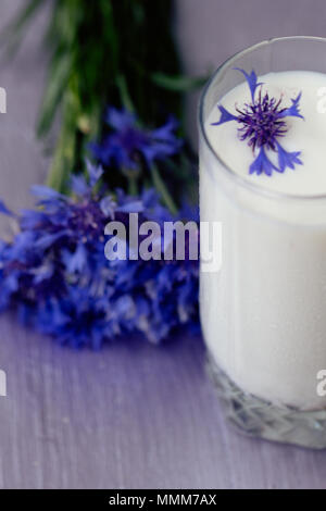 glass of milk and a bouquet of cornflowers on a purple table - Stock Photo